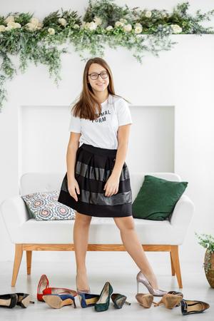 Chica elegante mide el zapato con tacones. Concepto de moda, compras, ropa, estilo de vida, centro comercial. Foto de archivo
