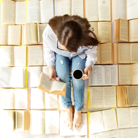 A young girl reads a book and drinks coffee. Top view. Concept for World Book Day, lifestyle, study, education Stock Photo