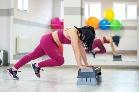 Adult woman is engaged in fitness in the gym. The concept of sports, a healthy lifestyle, losing weight Фото со стока