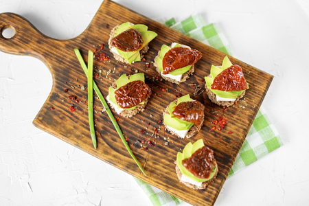 Appetizers with cheese, avocado and dried tomatoes on the board. Concept for food, healthy food and vegetarians. Imagens