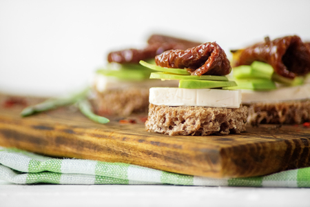 Hearty sandwiches with cheese, avocado and dried tomatoes. Concept for food, healthy food and vegetarians.