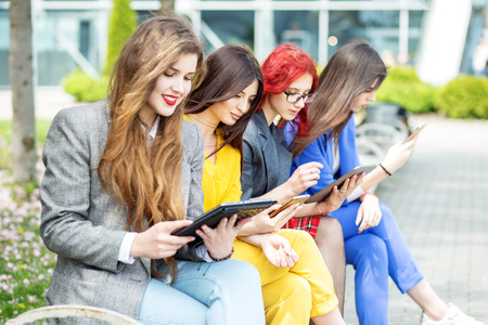 Four beautiful girls with gadgets are sitting on the bench. The concept of the Internet, social networks, study and lifestyle.