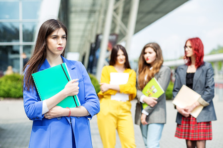 Young woman in a blue suit. Student with a folder. Education concept, exams, friendship and group of people. 写真素材