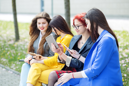 Beautiful girls sit and chat with gadgets on the bench. The concept of the Internet, social networks, study and lifestyle. 写真素材