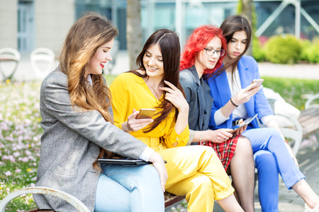 Beautiful girls are sitting with gadgets on the bench. Women communicate. The concept of the Internet, social networks, study and lifestyle.