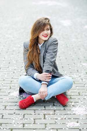 Happy girl is drinking hot coffee and smiling. Sits on the floor. Concept of lifestyle, urban, leisure, students.