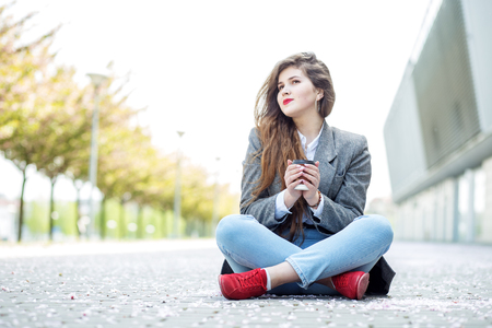 Happy girl sits on the floor with coffee and dreams. Concept of lifestyle, urban, leisure, students.