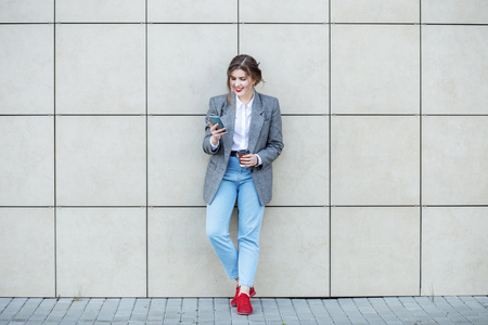 Adult woman stands near the wall with coffee. Communicate on the Internet. Concept of lifestyle, urban, business, study.