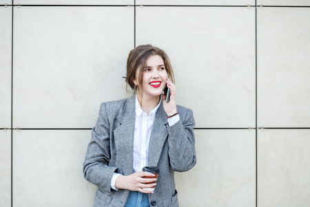 Adult woman stands near the wall with coffee. Communicate by phone. Copy space. Concept of lifestyle, urban, business, study. 写真素材