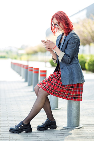 Beautiful teen girl looks through information in her smartphone. Concept of lifestyle, urban, internet, social network and study.