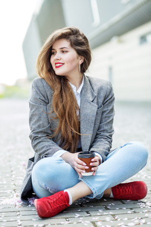 Beautiful girl with very long hair. To drink coffee. Concept of lifestyle, urban, leisure, students.
