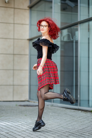 Teen girl bounces on the street. Red hair. Concept of lifestyle, urban, travel, fashion. 写真素材