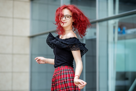 A girl is dancing on the street. Red hair. Concept of lifestyle, urban, travel, fashion. 写真素材
