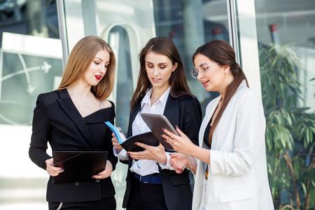 Equipo empresarial trabajando en un proyecto. Tres jóvenes con dispositivos. Concepto de negocio, marketing, finanzas, trabajo, colegas y estilo de vida. Foto de archivo