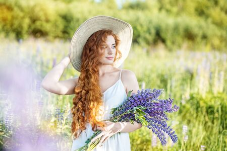 Beautiful girl with a bouquet of lupins flowers. Woman with long hair. Concept summer, lifestyle, travel and beauty.