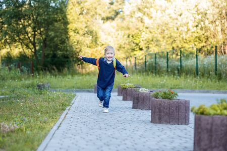 A happy child is running with a backpack. The concept of learning, school, mind, lifestyle and success. Standard-Bild