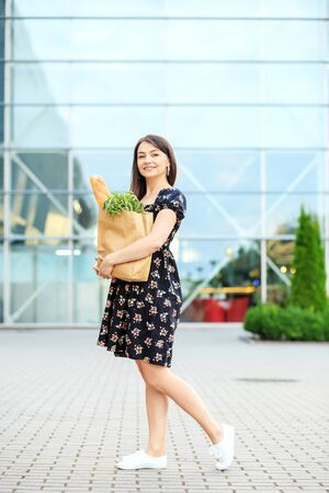 Woman holding bag with baguette and food. A girl in a dress. The concept of shopping, lifestyle.