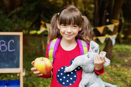 Cheerful first grader with a backpack and an apple. Back to school. The concept of education, school, childhood