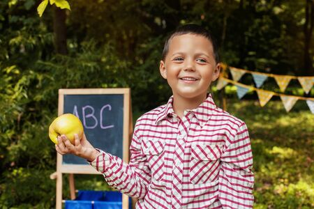 Cheerful schoolboy with an apple. Back to school. The concept of education, school, childhood Фото со стока
