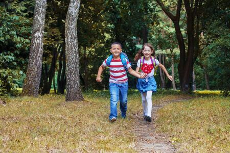 Children run with backpacks. Boy and girl. Back to school. The concept of education, school, childhood Фото со стока