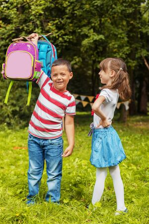 A strong child picks up two backpacks. Boy and girl Back to school. The concept of education, school, childhood