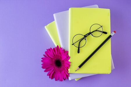 Interesting books, pencil and reading glasses and flower. Violet background. Concept back to school, education, international book day.