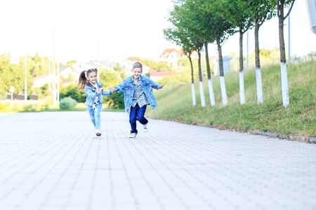 Children run holding hands. The concept of childhood, family, education.