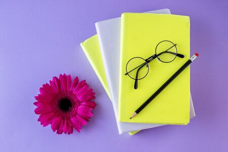 Interesting books, pencil and reading glasses and flower. Purple background. Concept back to school, education, international book day. 写真素材