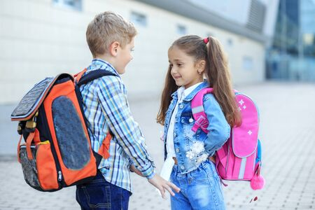 Classmates met in the schoolyard. Little boy and girl. The concept is back to school, study, friendship. Фото со стока