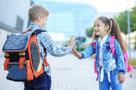 Friends met and give five. Little boy and girl. The concept is back to school, study, friendship.