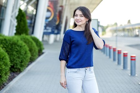 Beautiful girl in a blue t-shirt. Woman on the street. Concept for lifestyle, fashion and beauty.
