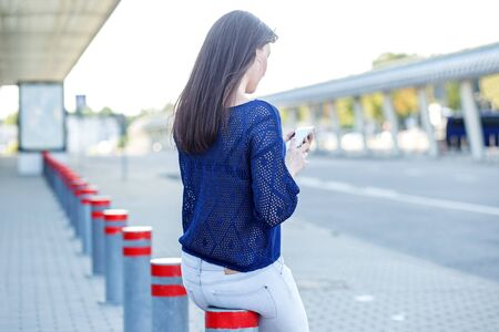 Beautiful girl with a smartphone. Woman on the street. Concept for lifestyle, fashion and communication.
