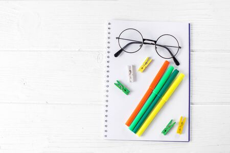 Green and yellow markers, notebook and glasses. The concept of school, creativity, childhood and work. Фото со стока