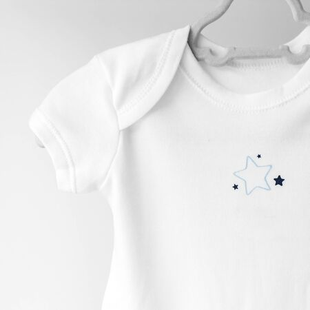 White clean clothes for a newborn on a hanger. The concept of clothes, motherhood, fashion and newborn.