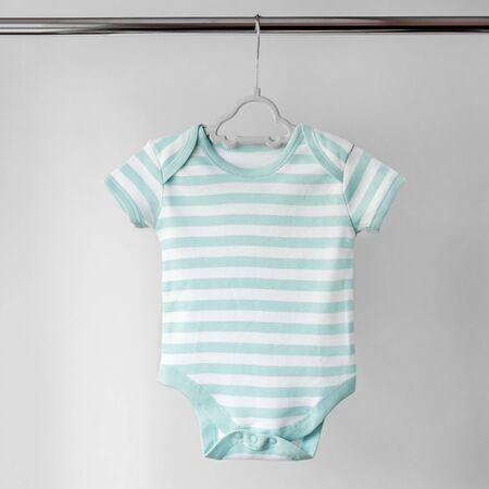 Striped clean clothes for a newborn on a hanger. The concept of clothes, motherhood, fashion and newborn.