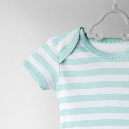 Striped clean clothes for a newborn on a hanger. Place for text. The concept of clothes, motherhood, fashion and newborn. Фото со стока