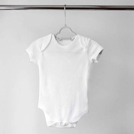 White clean clothes for a newborn on a hanger. Copy space. The concept of clothes, motherhood, fashion and newborn.