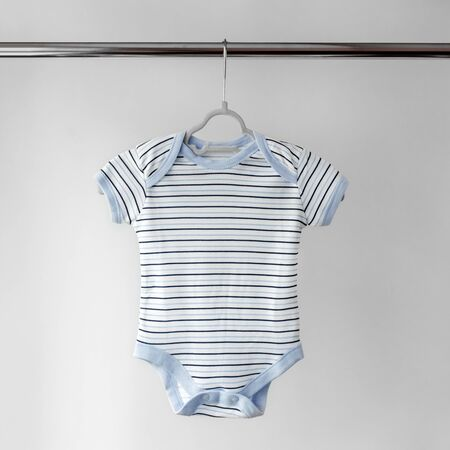 Childrens bodysuit for a baby in a strip. The concept of clothes, motherhood, fashion and newborn.