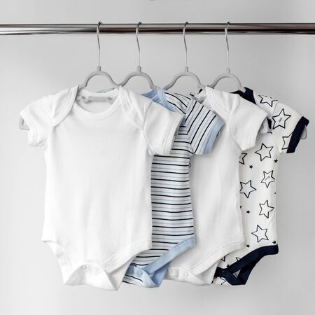 A set of beautiful clothes for a newborn on hangers. Copy space. The concept of clothes, motherhood, fashion and newborn Фото со стока