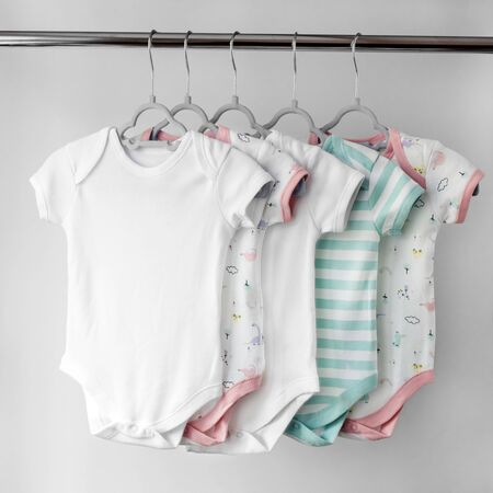 A set of beautiful clothes for a newborn girl on hangers. Copy space. The concept of clothes, motherhood, fashion and newborn. Фото со стока
