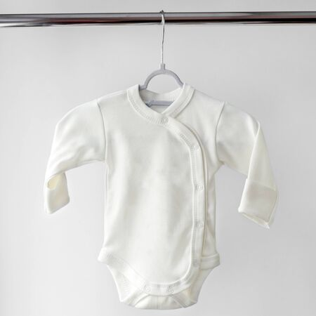 White body with long sleeves for a newborn on hangers. Copy space. The concept of clothes, motherhood, fashion and newborn.