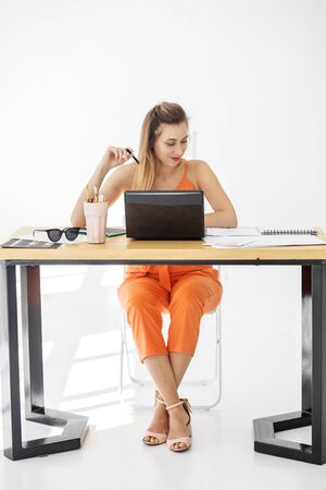 A young woman sits at an office desk and works. Concept for business, work, career and success. Фото со стока