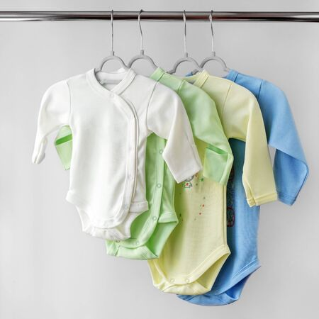 Set of colored bodysuits with long sleeves for the newborn. Copy space. The concept of clothes, motherhood, fashion and newborn. Фото со стока