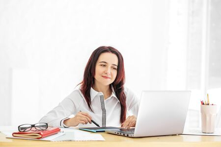A beautiful woman is sitting at her desk and smiling. Concept for business, work, career and success.