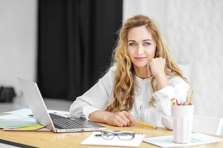 Beautiful woman sits at a desk. Concept for business, work, career and success. Фото со стока