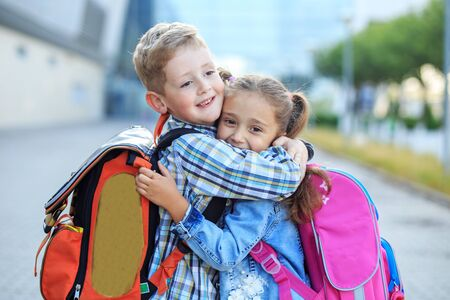 Children hug and laugh. Little boy and girl. The concept is back to school, study, friendship and family.