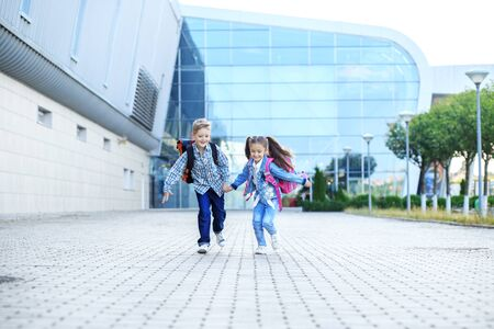 Children run with backpacks. Little boy and girl. The concept is back to school, study, friendship and family.