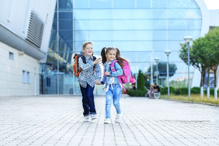 Children run with backpacks from school. Little boy and girl. The concept is back to school, study, friendship and family. Фото со стока