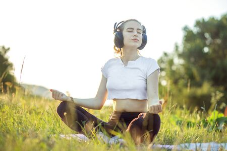 The girl listens to music on headphones. A woman is meditating. The connection of man and nature. Фото со стока