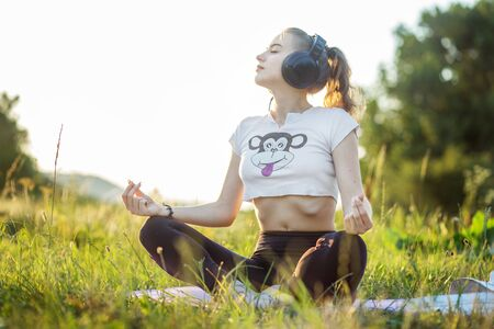 The girl listens to music on headphones. A woman is meditating. The combination of nature and man. Concept for lifestyle, music, relaxation. Фото со стока